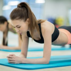 Pretty slim girl in activewear and her friend doing planks on blue mats while training in gym